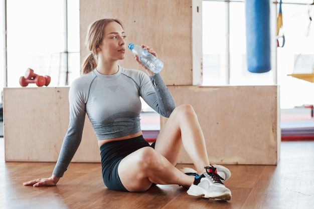 Перерыв. спортивная молодая женщина имеет фитнес-день в тренажерном зале в утреннее время
