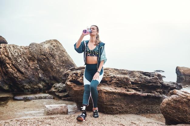 Принимая перерыв, усталая женщина-спортсмен-инвалид с протезом ноги пьет воду, сидя на