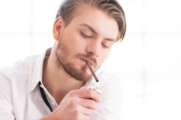 休憩して煙草を吸う。シャツとネクタイのハンサムな若い男がタバコに火をつける