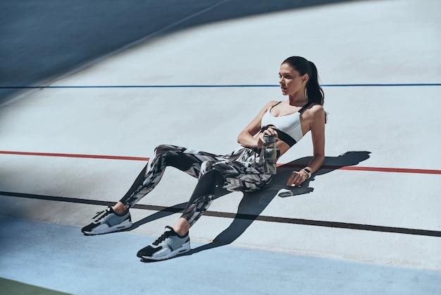 Сделать перерыв. вид сверху молодой женщины в расслабляющей спортивной одежде