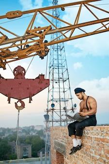 休憩を取って。建設現場のレンガの壁に座っている新聞を読んでいる筋肉のビルダーの垂直ショット