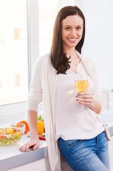 料理をしながら休憩。白ワインとグラスを保持し、キッチンに立って笑っている魅力的な若い女性