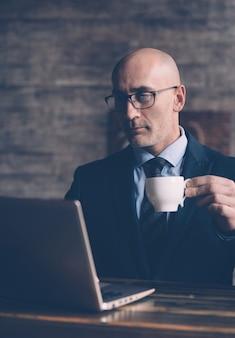 Во время перерыва на кофе и просматривая деловую переписку, бизнесмен держит в руке чашку кофе и смотрит в монитор ноутбука в очках.