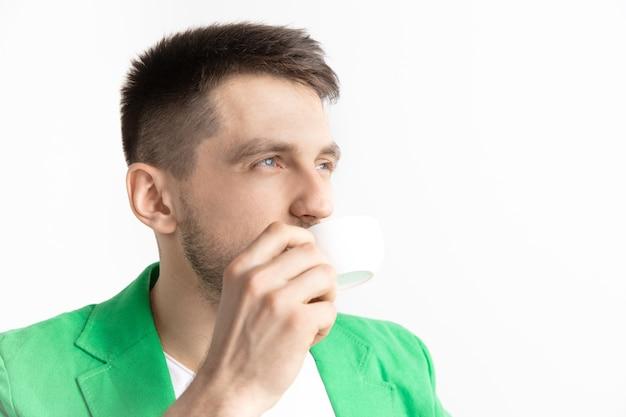 コーヒーブレイク。灰色の壁に立って笑って、コーヒーカップを保持しているハンサムな若い男