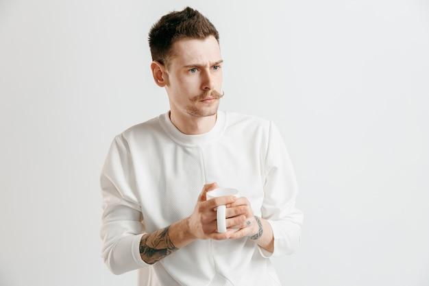 コーヒーブレイク。灰色のスタジオの背景に立っている間コーヒーカップを保持しているハンサムな若い男