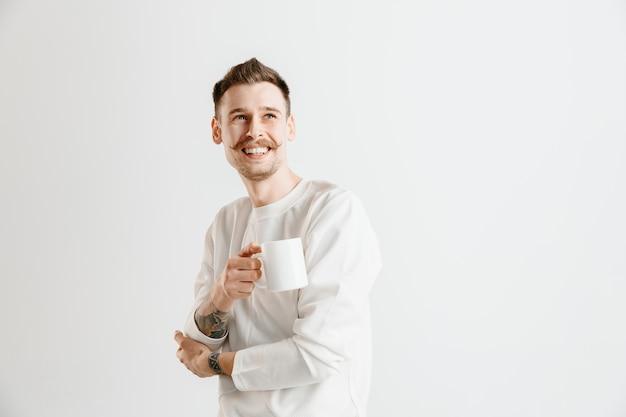 휴식을 취하십시오. 회색 스튜디오 배경에 서있는 동안 커피 잔을 들고 잘 생긴 젊은 남자