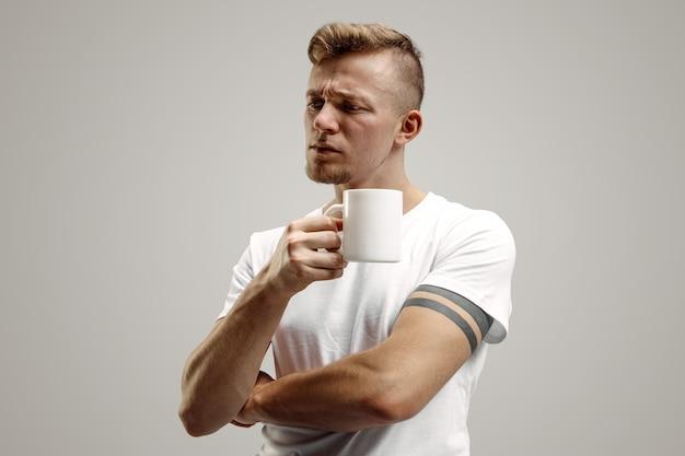 コーヒーブレイク。灰色のスタジオに立っている間コーヒーカップを保持しているハンサムな若い男