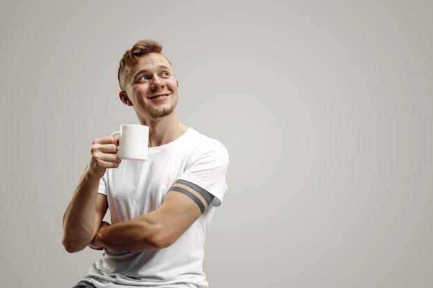 コーヒーブレイク。コーヒーカップを保持しているハンサムな若い男