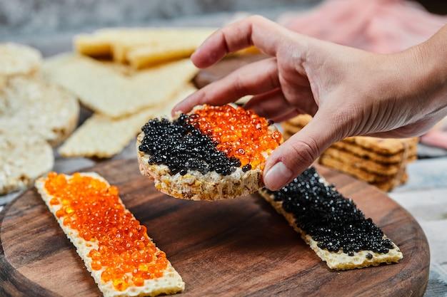 빨간색과 검은 색 캐비어와 함께 크래커 샌드위치를 먹는다.