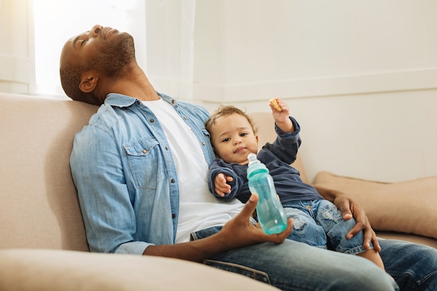 昼寝をしている。眠っていて、彼の幼い息子と彼のボトルを持って、ソファに座っている黒髪の疲れたアフリカ系アメリカ人の男