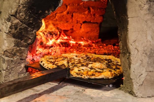 パラグアイの手作りオーブンからピザを取り出す-タタクア。