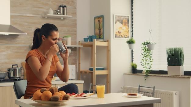 아침에 맛있는 아침 식사를 즐기면서 커피 한 모금. 아침에 커피 한 잔을 즐기는 레이디. 행복한 주부는 혼자 건강한 식사를 하며 휴식을 취하고 있다