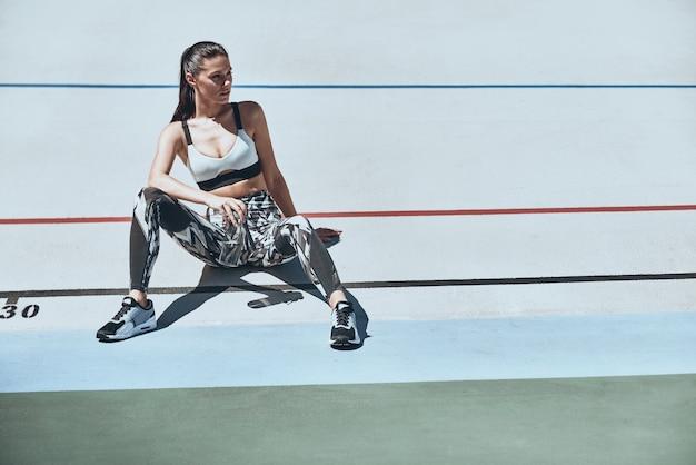 Взять тайм-аут. красивая молодая женщина в спортивной одежде, глядя в сторону