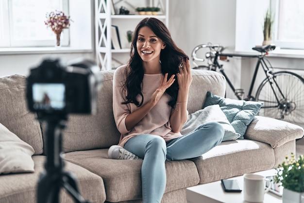 すべてについて取ります。屋内に座ってソーシャルメディアビデオを作る女性のvlogger