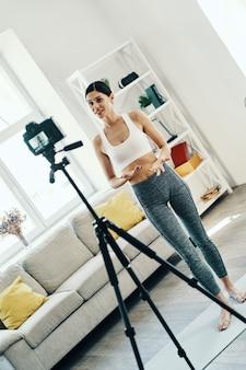スポーツについて。自宅で時間を過ごしながらソーシャルメディアビデオを作るスポーツウェアの美しい若い女性