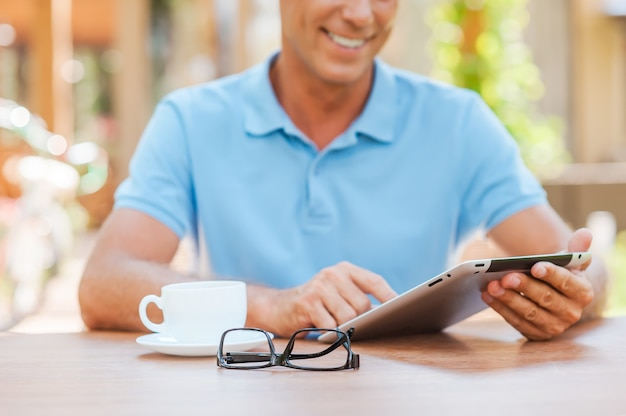 Taking advantages of free wi-fi. close-up of cheerful mature man writing something in his note pad and smiling while sitting at the table outdoors with house in the background