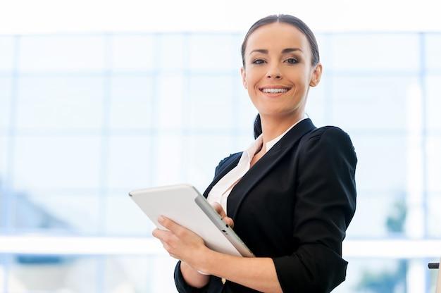 디지털 시대를 활용합니다. 디지털 태블릿을 들고 야외에 서 있는 동안 웃고 있는 정장을 입은 아름다운 젊은 여성