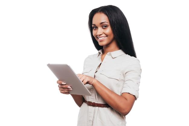 디지털 시대를 활용합니다. 디지털 태블릿에서 작업하고 흰색 배경에 서서 웃고 있는 자신감 있는 젊은 아프리카 여성
