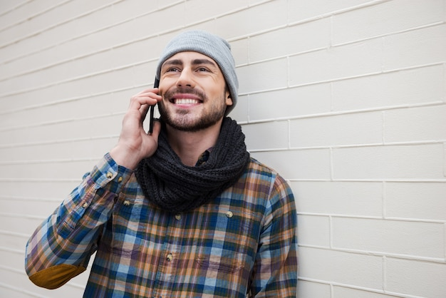 デジタル時代を利用する。携帯電話で話し、レンガの壁に寄りかかって笑っているハンサムな若い男