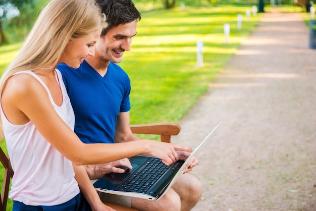 デジタル時代を利用する。一緒にベンチに座ってラップトップを見ている美しい若い愛情のあるカップルの側面図