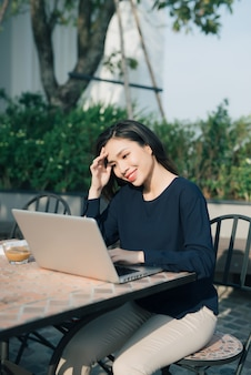 무료 wi-fi를 활용합니다. 노트북에서 작업하고 야외에서 앉아있는 동안 웃는 아름다운 젊은 여자