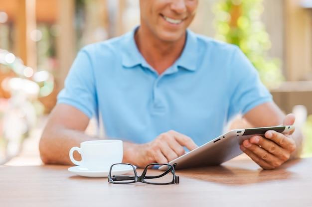 무료 wi-fi를 활용합니다. 그의 메모장에 뭔가를 쓰고 배경에 집과 야외 테이블에 앉아있는 동안 웃는 쾌활한 성숙한 남자의 클로즈업