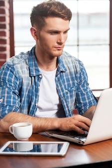 無料wi-fiを利用します。テーブルに座ってラップトップに取り組んでいるハンサムな若い男