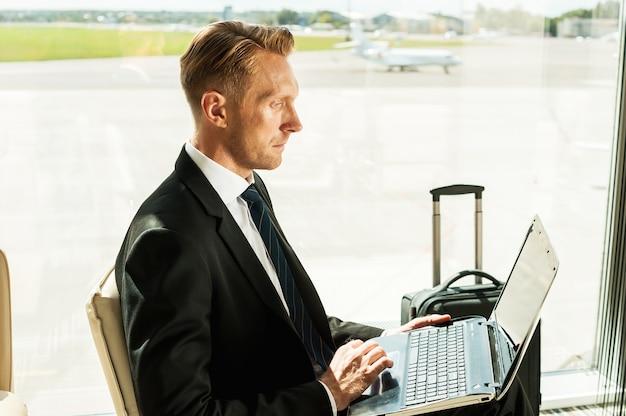 Воспользуйтесь преимуществами бесплатного wi-fi. вид сбоку уверенного в себе бизнесмена в формальной одежде, работающего на ноутбуке в ожидании рейса в аэропорту