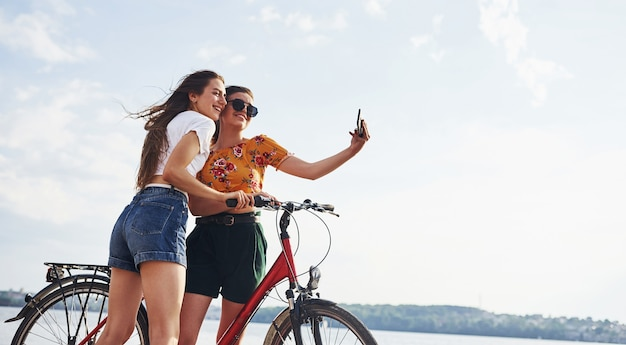 Taking amazing selfie. two female friends on the bike have fun at beach near the lake.
