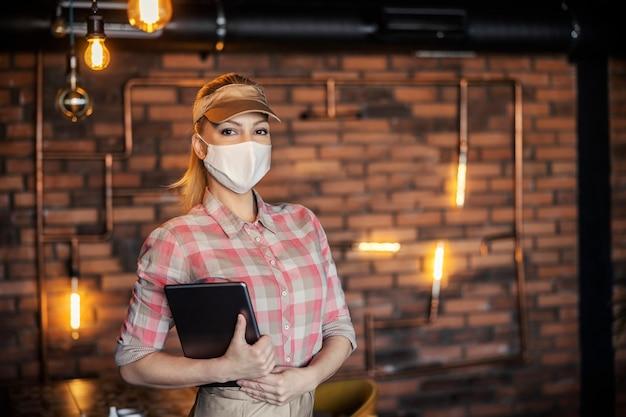 식당에서 주문하기. 얼굴 보호 마스크가 달린 파스텔 옷을 입은 여성 웨이트리스와 여주인의 초상화가 레스토랑에 서서 주문을 입력하는 디지털 태블릿을 들고 있습니다.