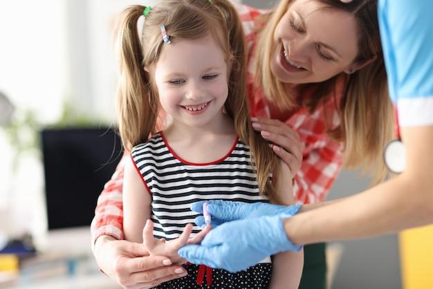 Взятие крови из пальца маленькой девочки для лабораторного анализа