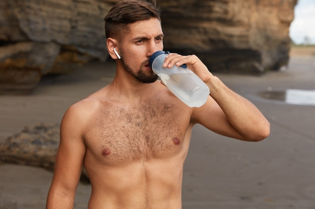激しいトレーニングの後に休憩を取る。疲れた若い男性アスリートはスポーティな体型をしています