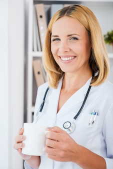 重い仕事から休憩を取る。カップを保持している白い制服を着た陽気な女医