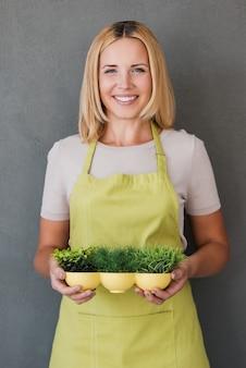 環境への配慮。植木鉢を保持している緑のエプロンで成熟した女性の笑顔