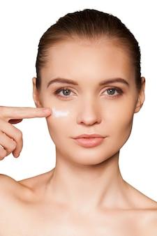 Заботится о ее лице. портрет красивой молодой женщины, намазывающей крем на лицо и смотрящей в камеру, изолированную на белом фоне