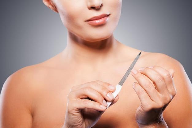Уход за ногтями. обрезанное изображение зрелой женщины, завернутой в полотенце, полируя ногти, стоя на сером фоне