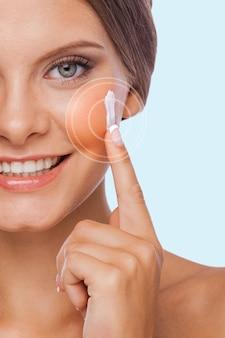 Заботится о ее коже. обрезанное изображение молодой женщины, намазывающей крем на лице и улыбающейся, стоя на белом фоне