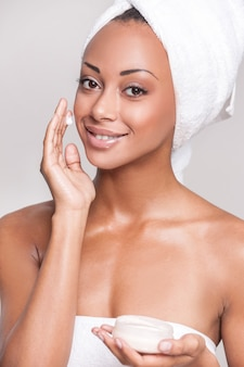 Заботится о ее коже. портрет красивой молодой афро-американской женщины, завернутой в полотенце, намазывающей крем на лицо и улыбающейся, изолированной на сером фоне