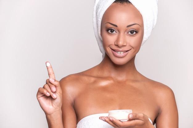 Заботится о ее коже. портрет красивой молодой афро-американской женщины, завернутой в полотенце со сливками на пальце