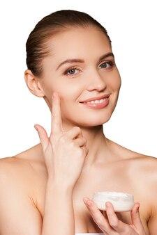 Заботится о ее коже. портрет красивой молодой женщины, завернутой в полотенце, намазывающий крем на лицо и улыбающийся, пока изолирован на белом фоне