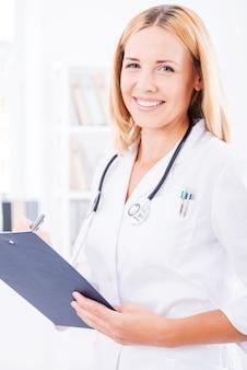 あなたの健康の世話をします。カメラを見て、笑顔の白い制服を着た陽気な女医師