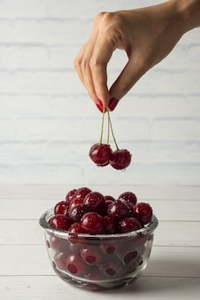 Taking cherries from a glass bowl isolated on white background