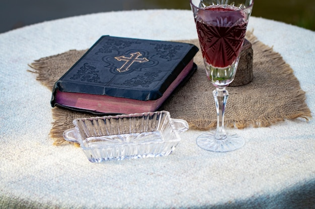 Taking communion. cup of glass with red wine, bread and holy bible on wooden table close-up.
