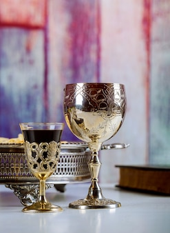 Taking communion. cup of glass with red wine, bread on wooden table focus on wine