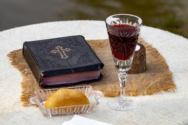 聖体拝領。木製のテーブルのクローズアップに赤ワイン、パン、聖書とガラスのカップ。