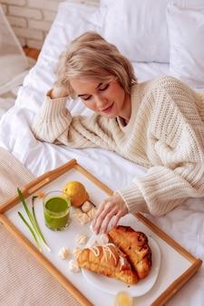 クロワッサンを取る。ベッドで冷やしながら朝クロワッサンを取る若いブロンドの髪のスリムな女性