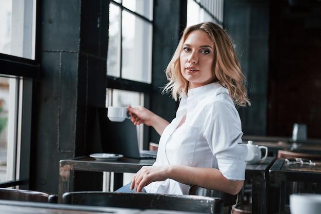 一杯のコーヒーを取ります。昼間のカフェで室内に金髪の巻き毛を持つ実業家。