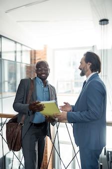 Прием документов. темнокожий бизнесмен в очках принимает документы у своего партнера