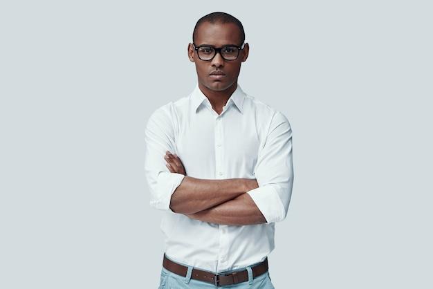 Относиться ко всему серьезно. красивый молодой африканский мужчина смотрит в камеру, стоя на сером фоне