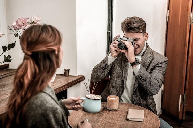Фотосъемка на пленку. мужчина фотографирует женщину с помощью пленочной камеры